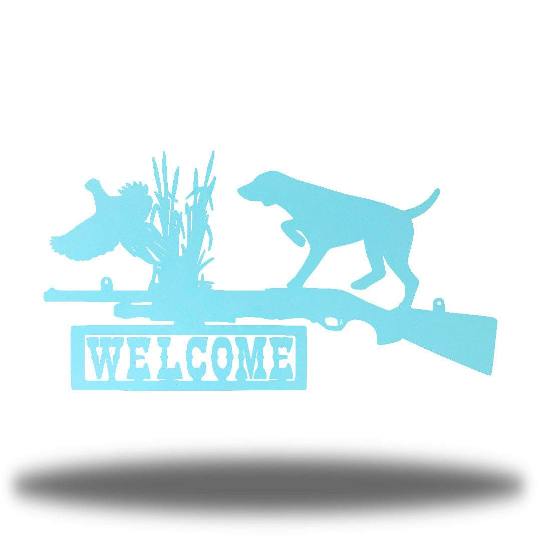 "Light blue steel wall art decoration that features a dog, duck and shotgun with the word ""WELCOME"" on it"