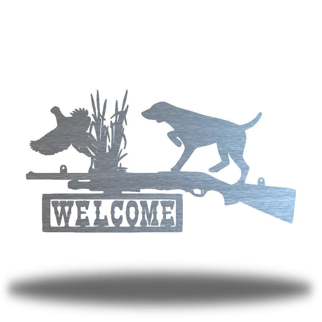 "Silver steel wall art decoration that features a dog, duck and shotgun with the word ""WELCOME"" on it"