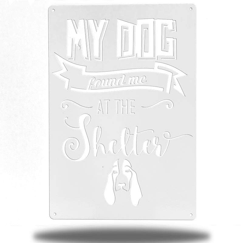 "White wall decoration signage has a basset hound and texts ""MY DOG found me AT THE Shelter"" on it"