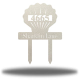 "Silver scallop-shaped yard stake address sign with the texts ""4665 Sharkfin Lane"""