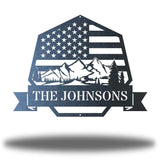 "Black heptagonal-shaped US flag wall decor featuring outdoor scenery and the texts ""THE JOHNSONS"""