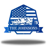 "Blue heptagonal-shaped US flag wall decor featuring outdoor scenery and the texts ""THE JOHNSONS"""
