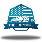 "Teal heptagonal-shaped US flag wall decor featuring outdoor scenery and the texts ""THE JOHNSONS"""
