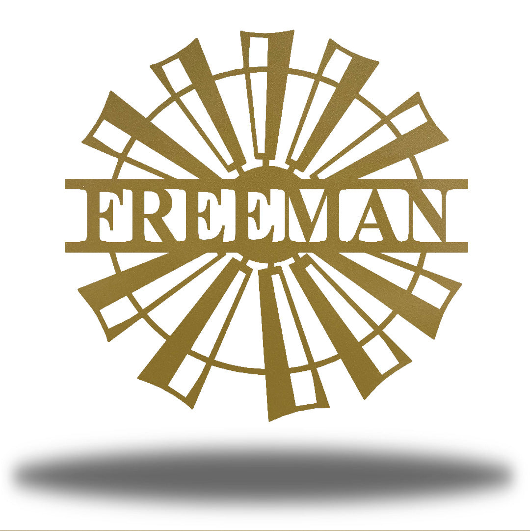 "Gold windmill-shaped monogram with the name ""FREEMAN"" on it"