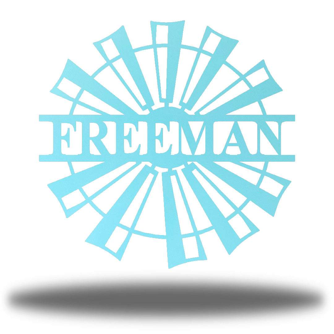 "Light blue windmill-shaped monogram with the name ""FREEMAN"" on it"