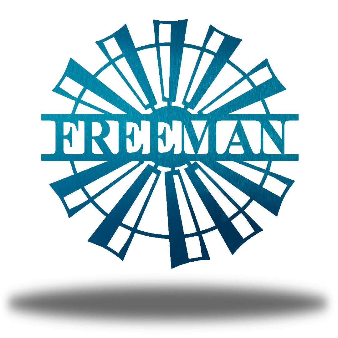 "Teal windmill-shaped monogram with the name ""FREEMAN"" on it"