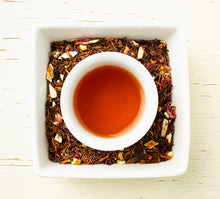 Load image into Gallery viewer, South African herbal rooibos with orange peel, hibiscus and rose petals and mug of the brewed dark red tea viewed from above.