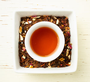 South African herbal rooibos with orange peel, hibiscus and rose petals and mug of the brewed dark red tea viewed from above.