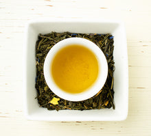 Load image into Gallery viewer, Birdseye view of mug of Boulder Blues tea on whole leaf Sencha and Dragonwell green tea accented with blue and yellow petals.