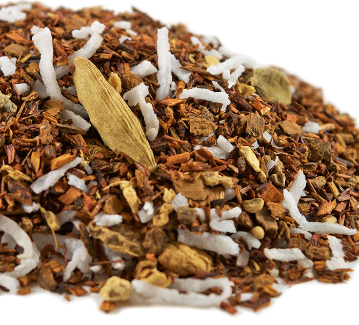Closeup of mound of herbal blend of loose South African red rooibos, ginger root chucks, cinnamon bark, and coconut flakes.
