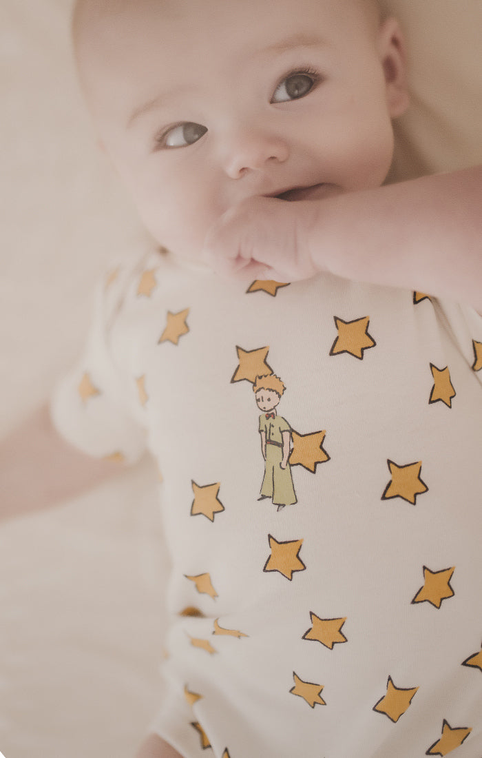 image of baby wearing onesie with all over star print and famous literary character The Little Prince on front