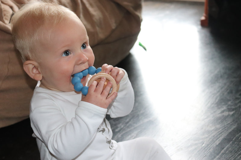 baby smiling and chewing on fashionable teether toy