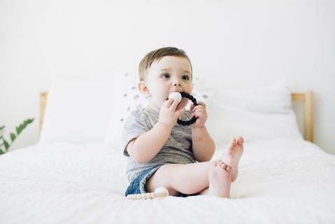 baby chewing on black teether rattle ring