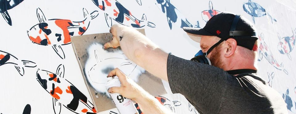Street Artist Jeremy Novy spray paints his signature koi stencil on a mural.