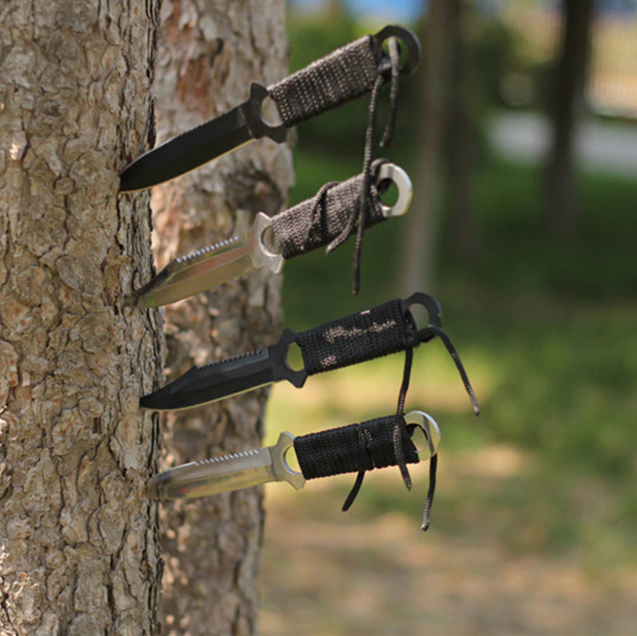 4 norse hawk tactical throwing knives sticked on a tree trunk