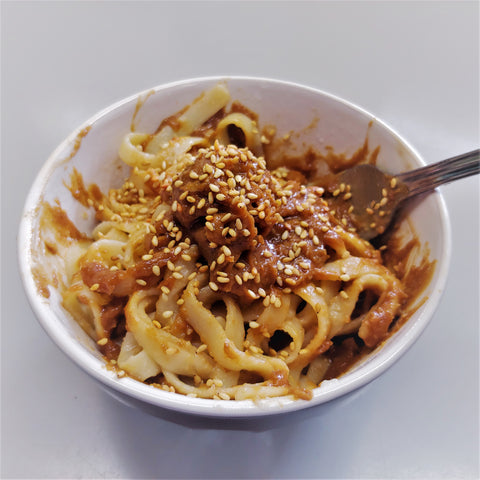 Noodles with peanut sauce and garnished with sesame seeds.