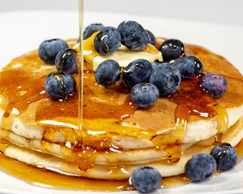 Stack of pancakes with blueberries and maple syrup.