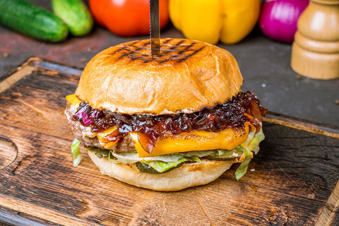 A hamburger sandwich that has been topped with caramelized onions.