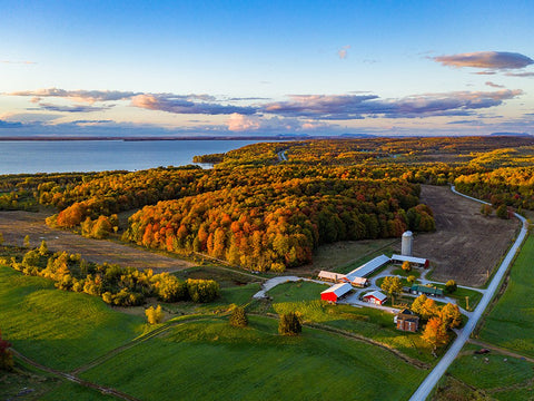 Drone shot of the Carman Brook Farm and the Missisquoi Bay in full fall foliage.