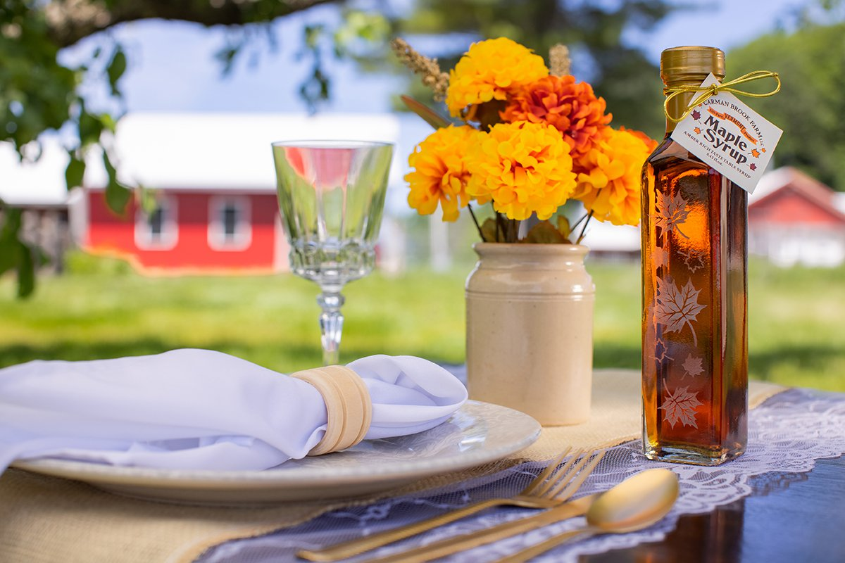 Wedding favor of maple syrup bottle with leaf motif at an outside place setting on a farm.