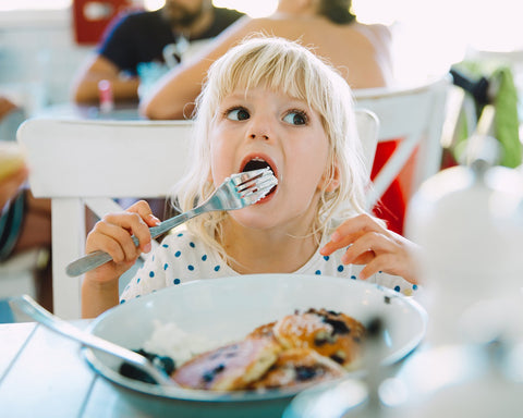 Little girl enjoying a plate of blueberry pancakes with cream.
