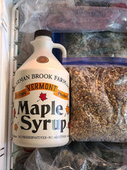 A plastic container of maple syrup stored in the freezer to preserve the freshness.