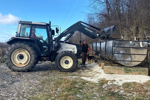 Daniel and Levon Fortin using a tractor to move a sap tank out to pumphouse one.