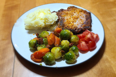 Plated dinner of roasted veggies, pork chops, mashed potatoes and cherry tomatoes.