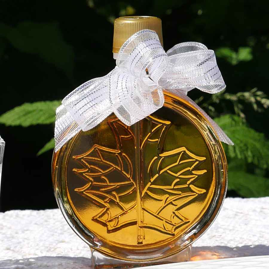 3D leaf bottle filled with Vermont maple syrup and embellished with a white ribbon.