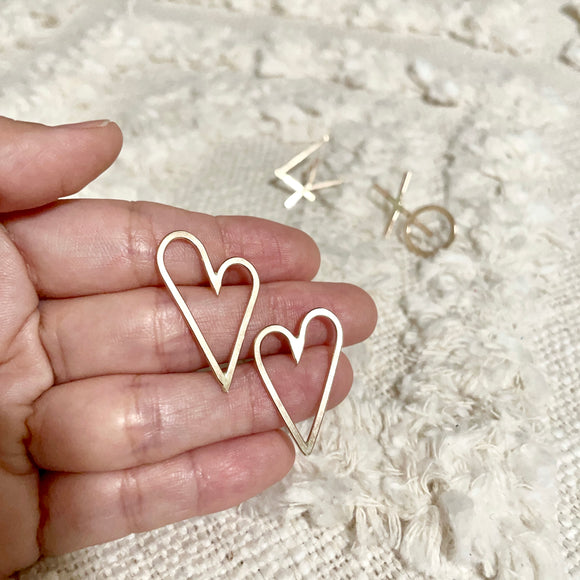 "Handwritten love letters are the perfect reminders that love is all around. Show your love without words. These Heart Earrings are very chic, classy and bold style. Two hearts one love♡︎     14k Gold Filled  Size: 1""H x 5/8""W     *handwritten collection pieces may have slight shape variations."
