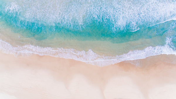 Arial photo of white water waves with sandy beach