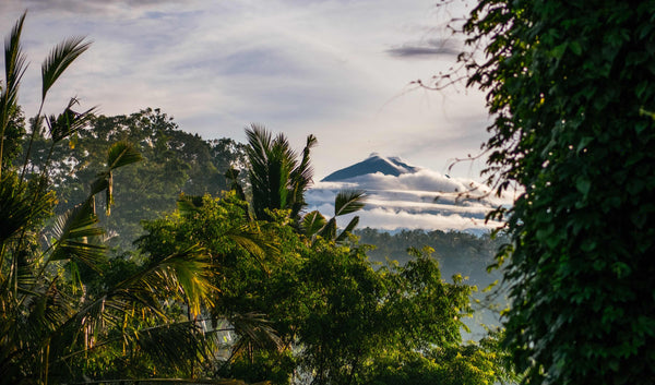 Volcano on the horizon with clouds and rainforest