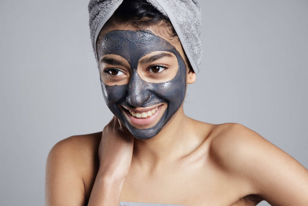 Lady with Kubu Restore Charcoal Face Mask with towel in hair