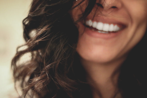 Smiling mouth of woman with wavy brown hair