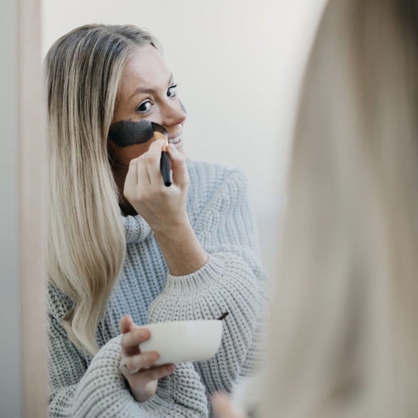 Woman applying face mask with brush and bowl in hand