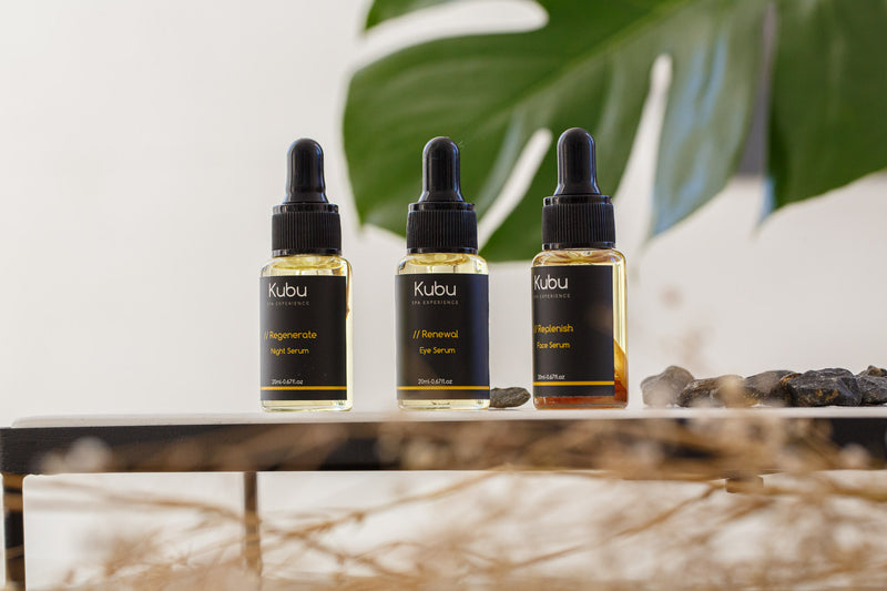 Kubu Essential Serum Trio bottles on bench with plant