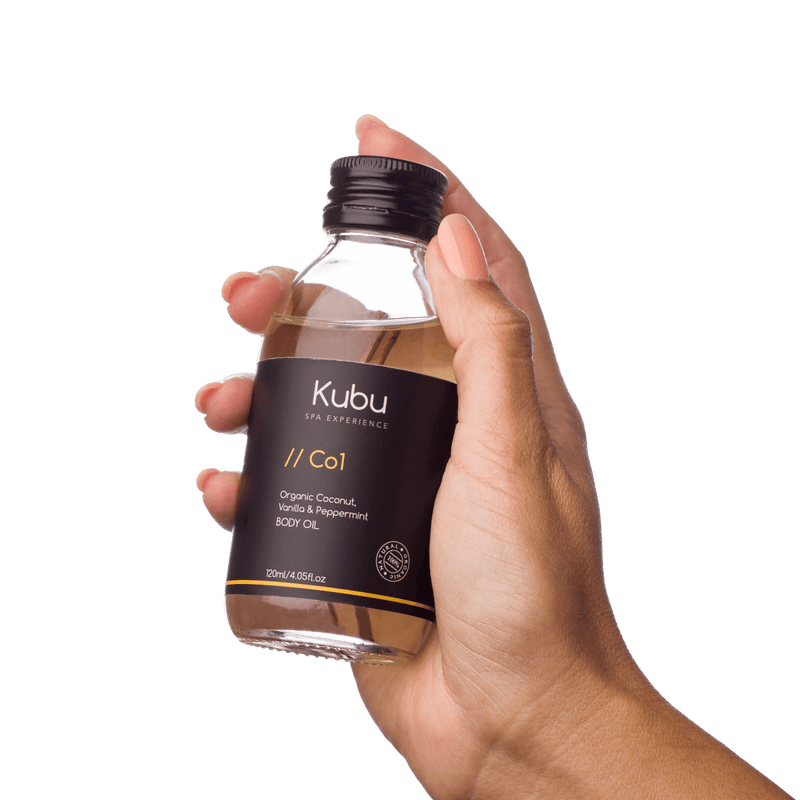 Bottle of Kubu Co1 Body Oil in lady's hand