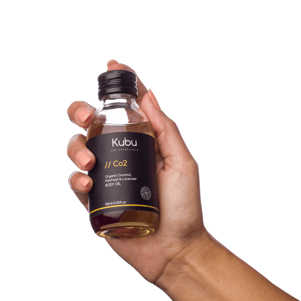 Bottle of Kubu Co2 Body Oil in lady's hand