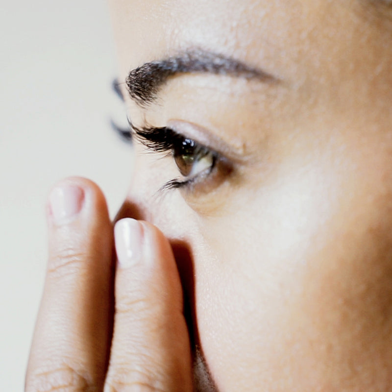 Lady applying Kubu Renewal Eye Serum with two fingers