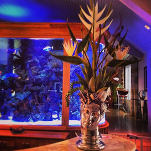 Tropical Floral Arrangement near Fish Tank in an Unusual Sculptural Container