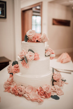Wedding Cake Flowers with Pink Hues, Silver Dollar Eucalyptus, Roses, and Rose Petals