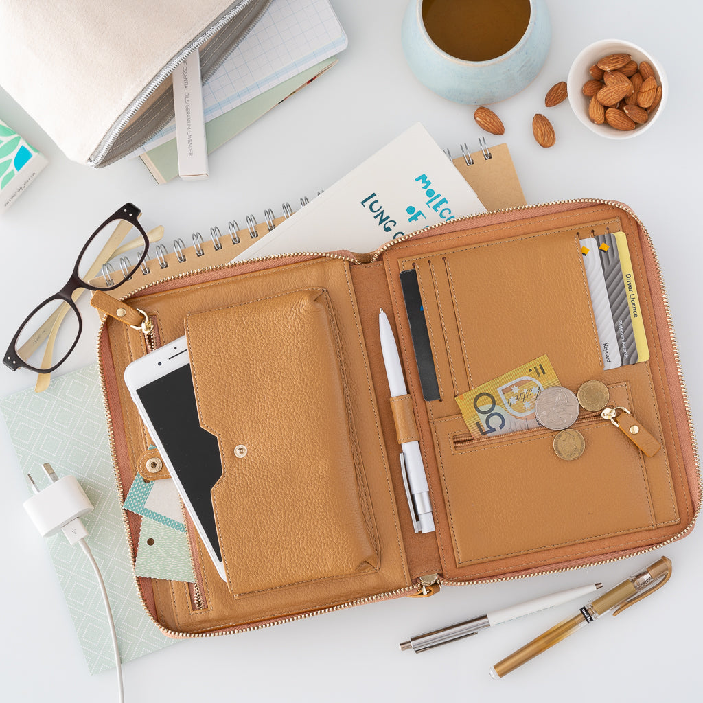 An opened pebbled leather travel wallet in camel on a white desk with pens, books, coffee and reading glasses.