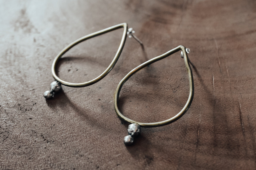 Teardrop shaped brass earrings with silver detail