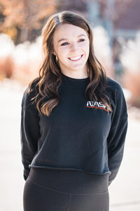 Women wearing a cropped NASA embroidered sweatshirt in black