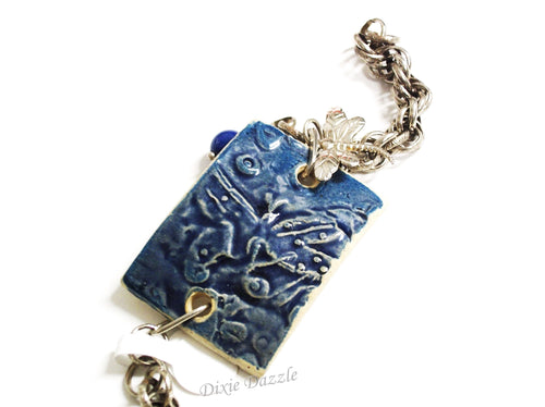 Textured ceramic bracelet in blue with dragonfly imprint and dragonfly charm