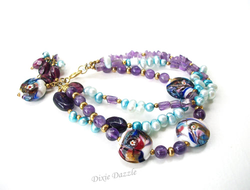Amethyst, freshwater pearls and lamp work beaded bracelet.  Triple strand aqua and purple bracelet with charms, made in America
