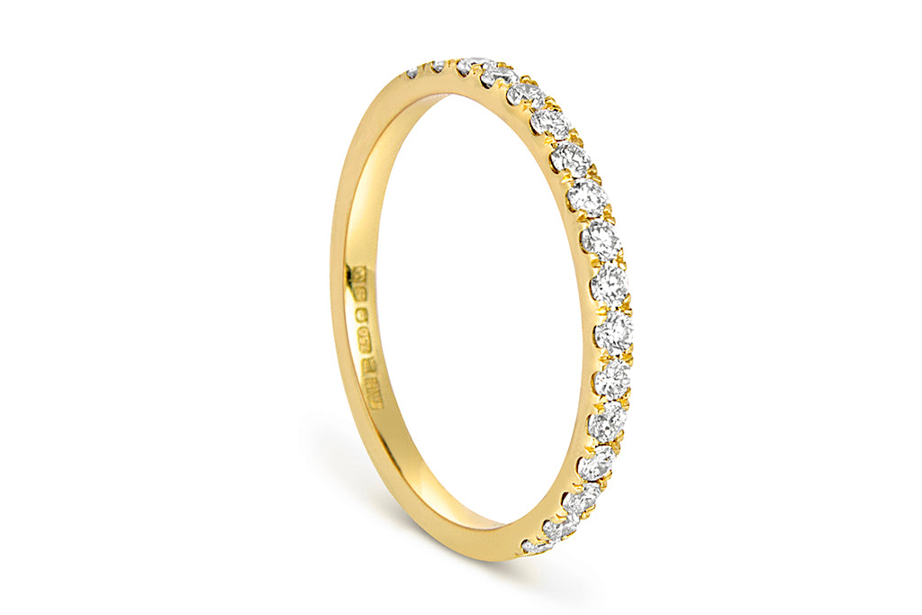 The half microset Altair eternity wedding band, cast in 18ct yellow Fairtrade Gold and set with conflict-free Canadian diamonds