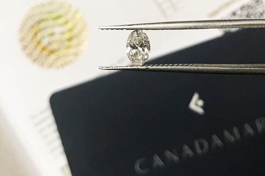 An oval-cut Canadian diamond with its Canadamark certificate