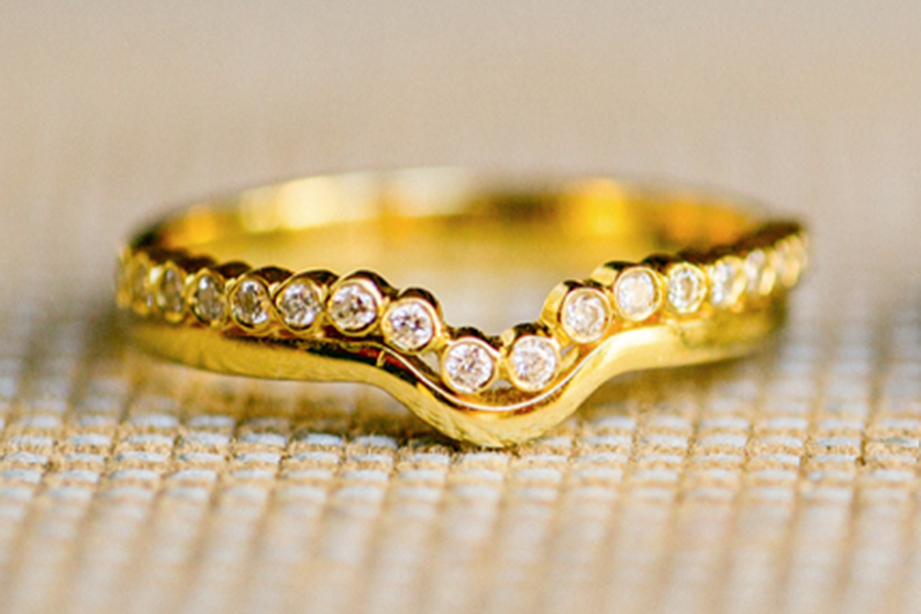 A bespoke eternity wedding band, shaped to complement the engagement ring. Cast in 18ct recycled yellow gold and adorned with African conflict-free diamonds in rub-over settings