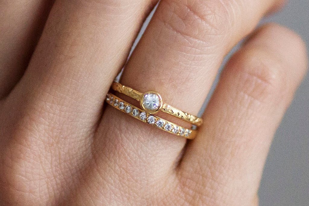 Hera engagement ring and Cherish eternity wedding band together on the ring finger both cast in 18ct recycled yellow gold and set with conflict-free Canadian diamonds